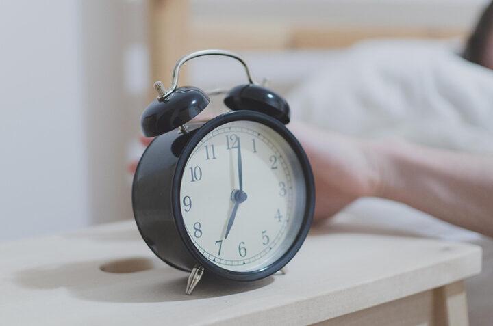 En hand är i fart med att sopa ner en väckarklocka från nattduksbordet.