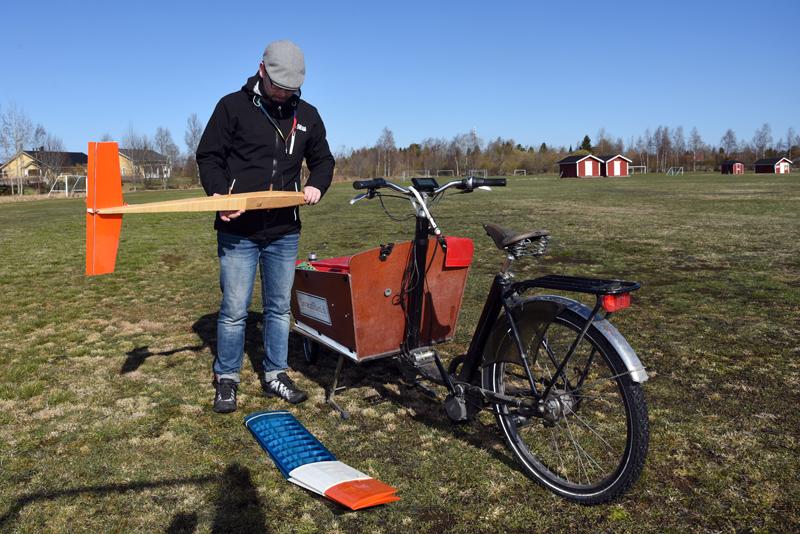 Roy Pietilä ottaa lennokin osia tavarapyörästään ja asettelee ne nurmikolle.