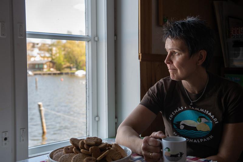 Lotta Söderlund istuu kahvipöydän ääressä ja katselee ikkunasta merelle.
