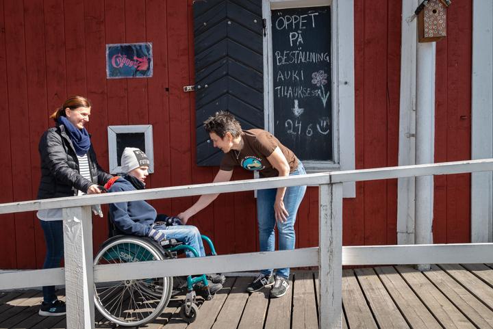 Lotta Söderlund kättelee pyörätuolissa istuvaa Julius Johanssonia, jota Nina Granström työntää ramppia ylös luontokeskukseen.