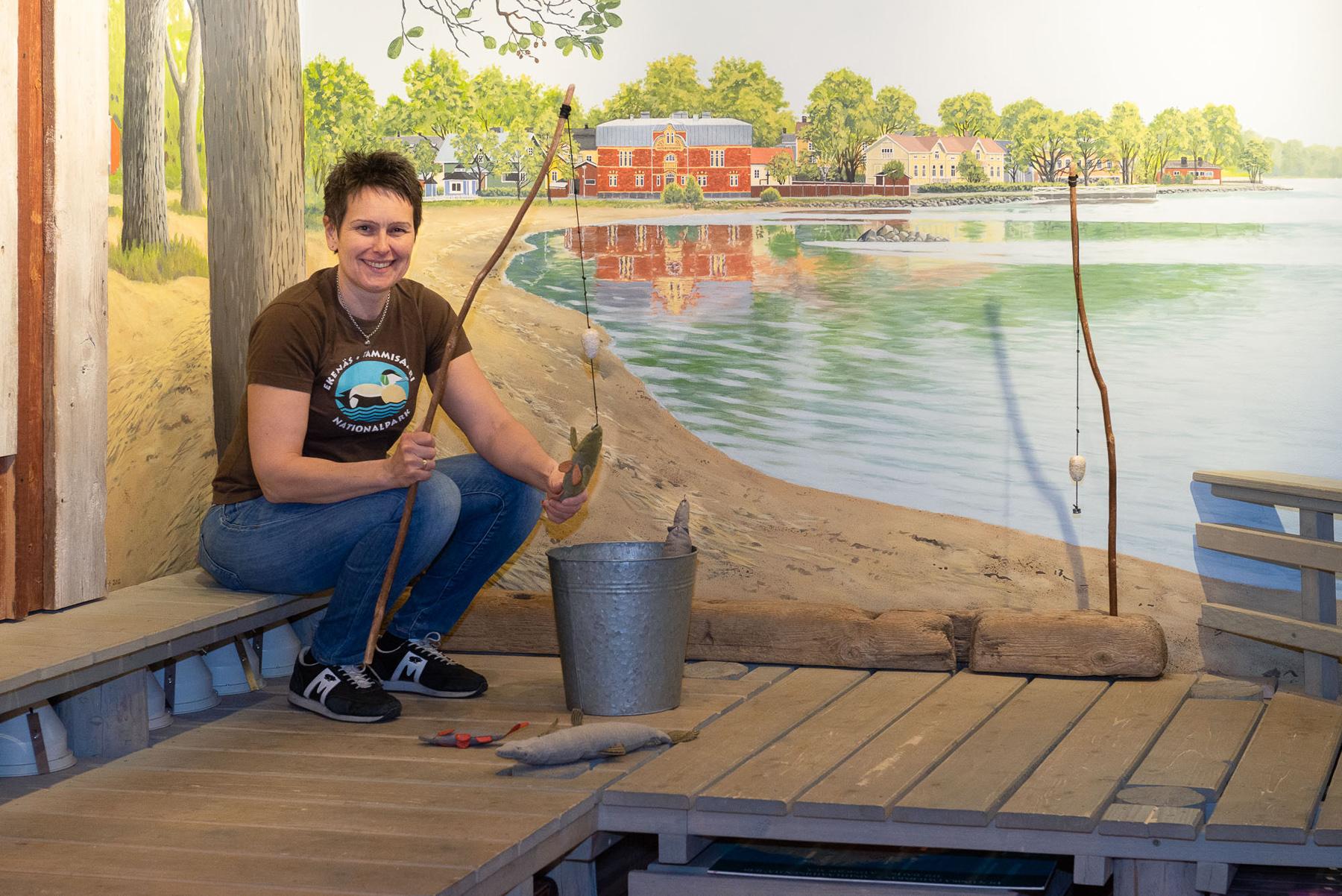 Lotta Söderlund kalastaa pehmolelukaloja luontokeskuksen sisään rakennetulla laiturilla.