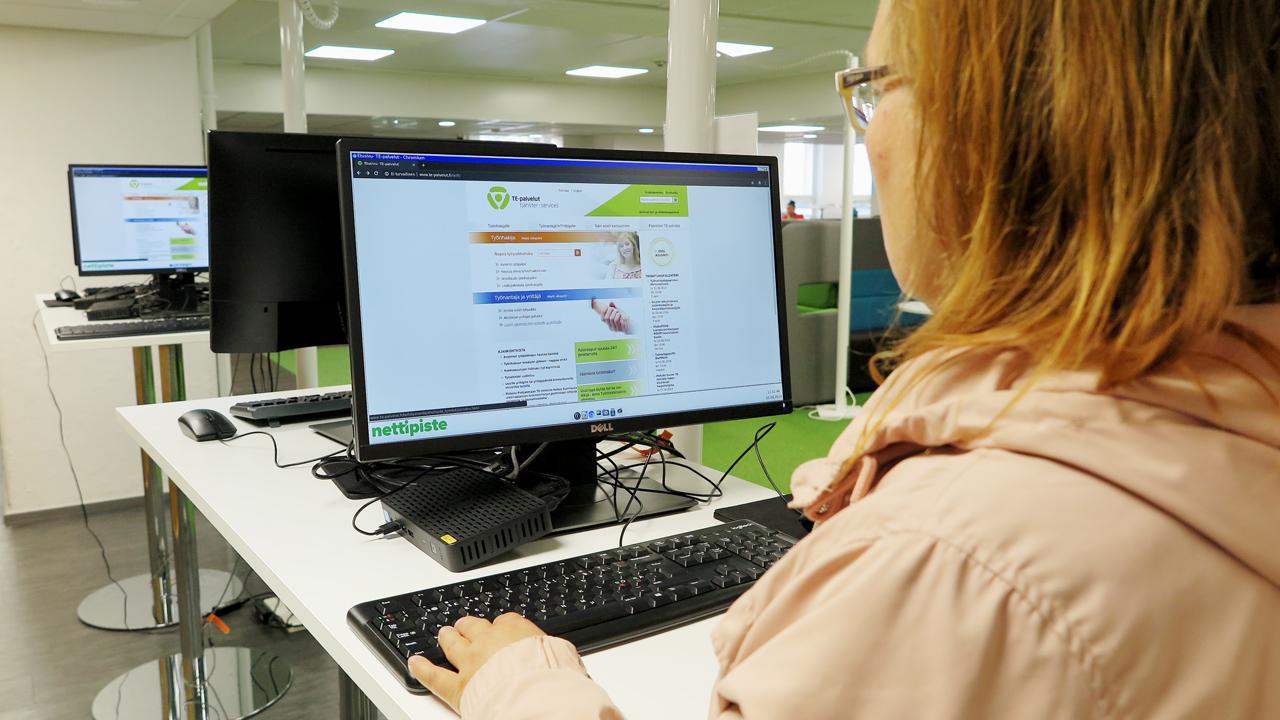 Työnhakija tietokoneella TE-toimistossa.