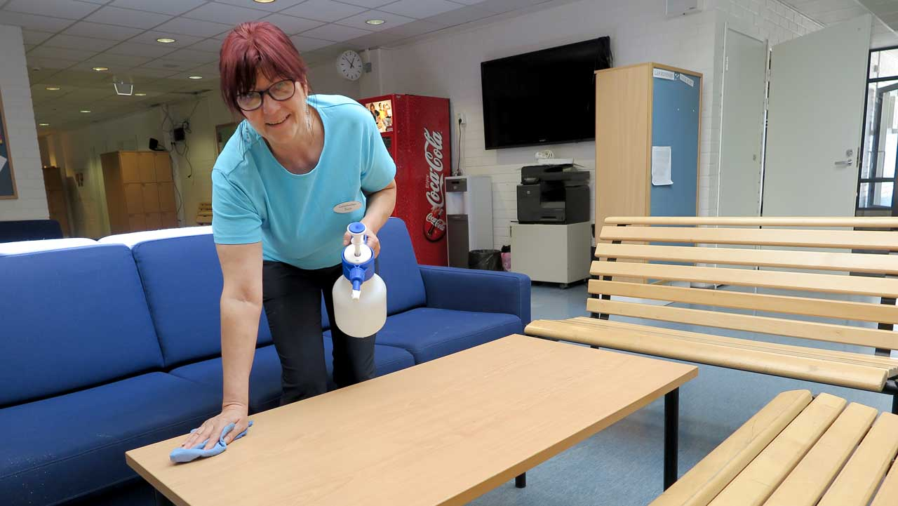 Onko kemikaalittomista siivousaineista hyötyä? Siivooja puhdistaa pöytää.