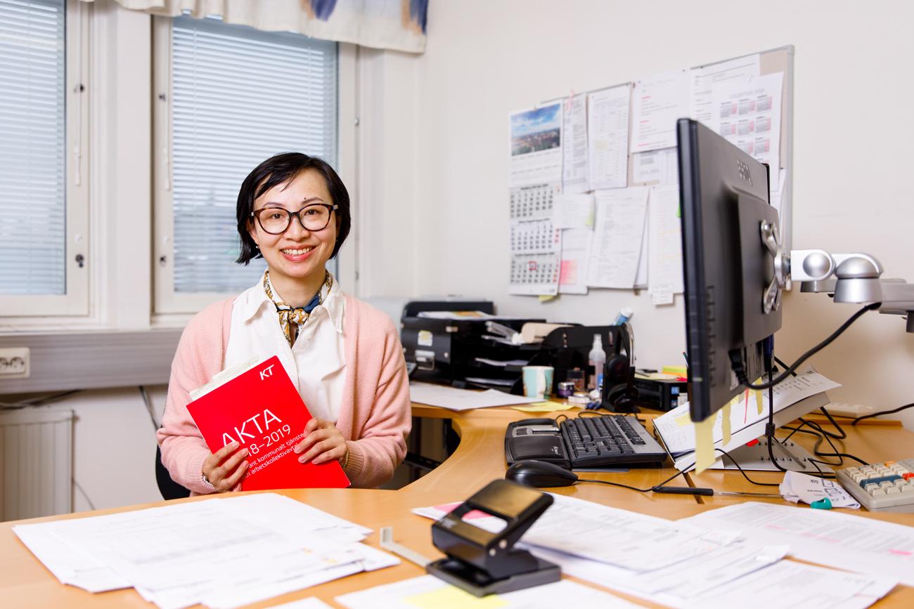 Jing Li sitter vid skrivbordet med kollektivavtalet AKTA i handen.
