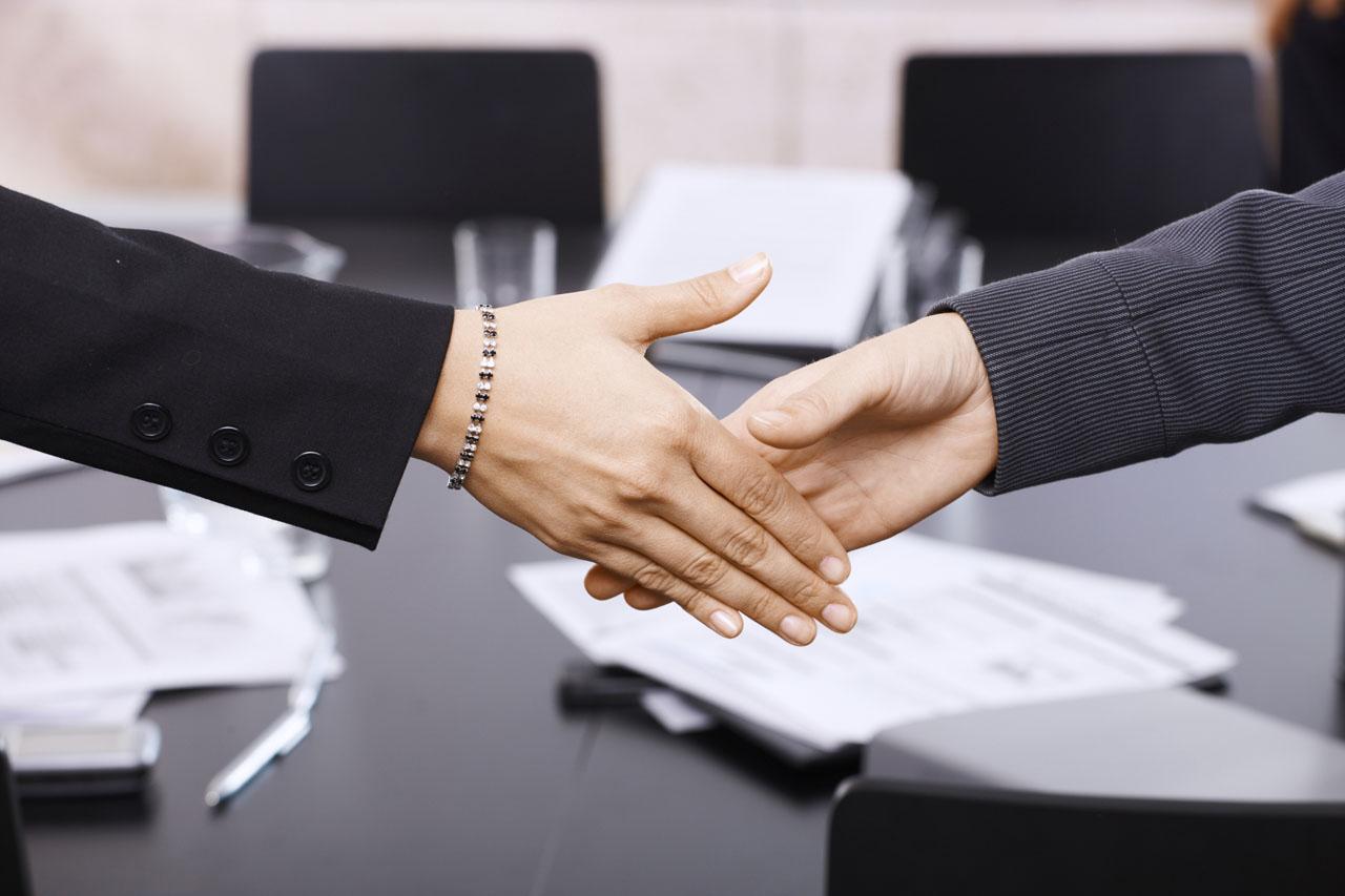 Kaksi naista kättelee.