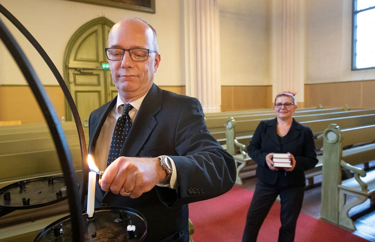 Christer Viksten sytyttää kynttilää lähetyskynttelikköön, Maria Viksten odottaa virsikirjojen kanssa kauempana.