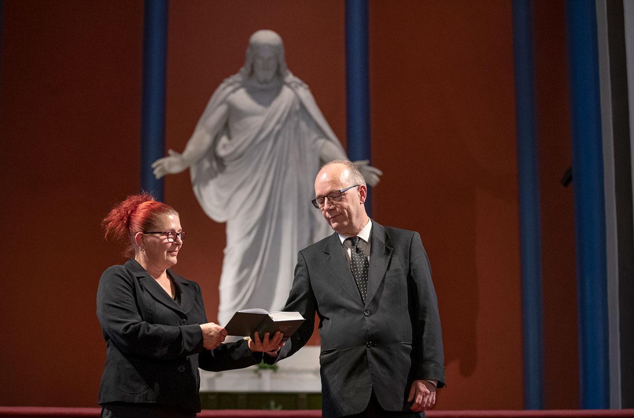 Maria och Christer Viksten läser i psalmboken framför Kristusstatyn i Lovisa kyrka.
