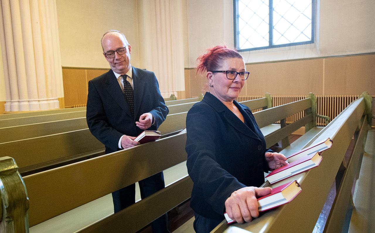 Christer ja Maria Viksten jakavat virsikirjoja kirkon penkkeihin.
