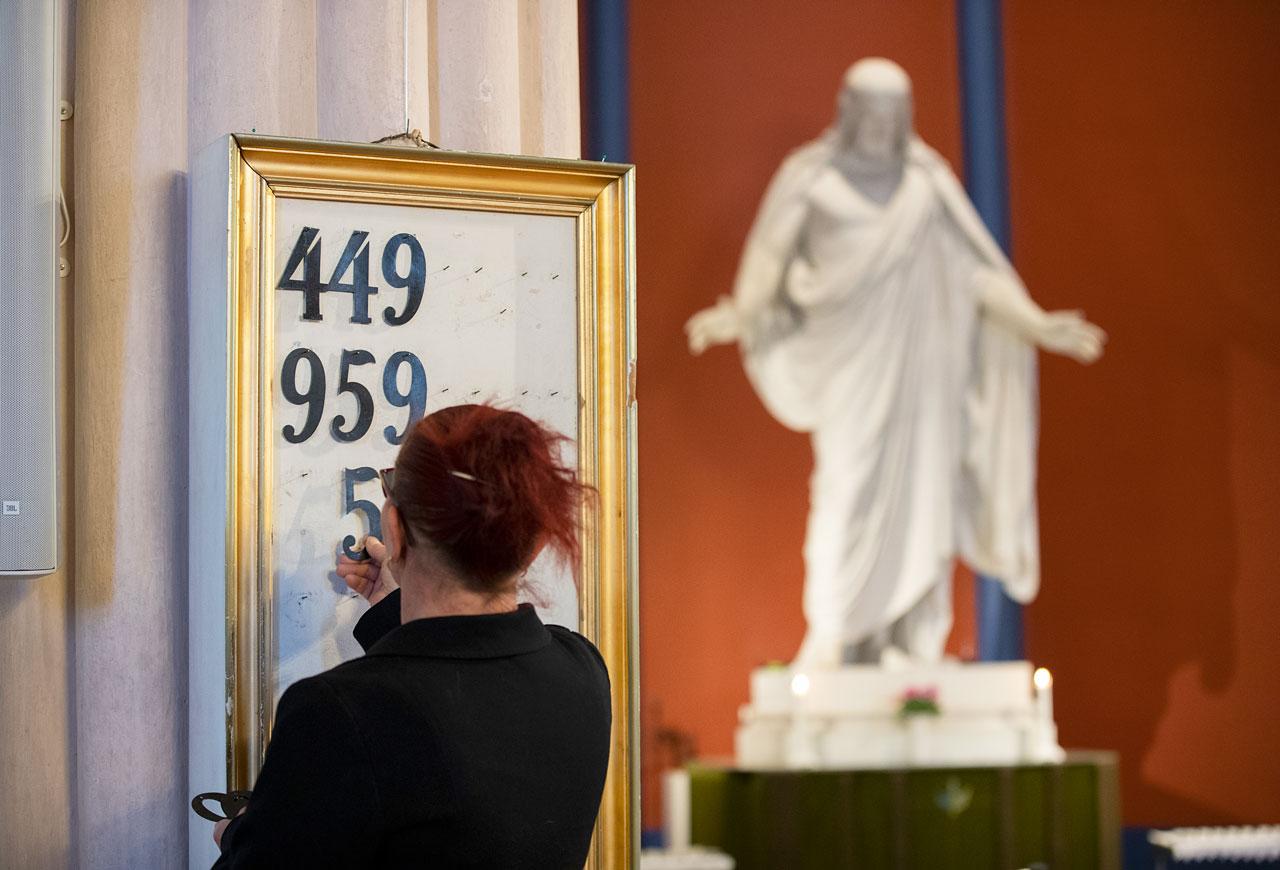 Maria Viksten hänger upp psalmsiffror på tavlan.
