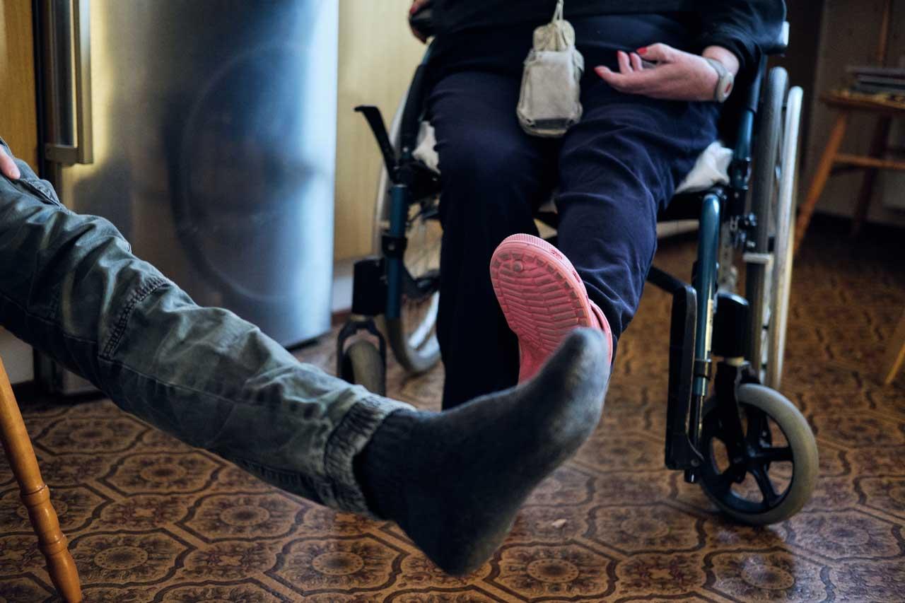 Lähihoitaja Nico Nordblad ja kuntoutettava Anne-Marie Påfs nostavat vasenta jalkaa vaakatasoon.