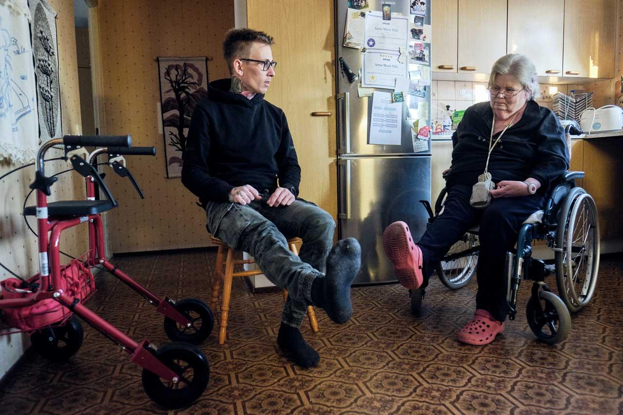 Lähihoitaja Nico Nordblad ja kuntoutettava Anne-Marie Påfs harjoittelevat tuoleissa istuen jalan nostamista vaakatasoon.