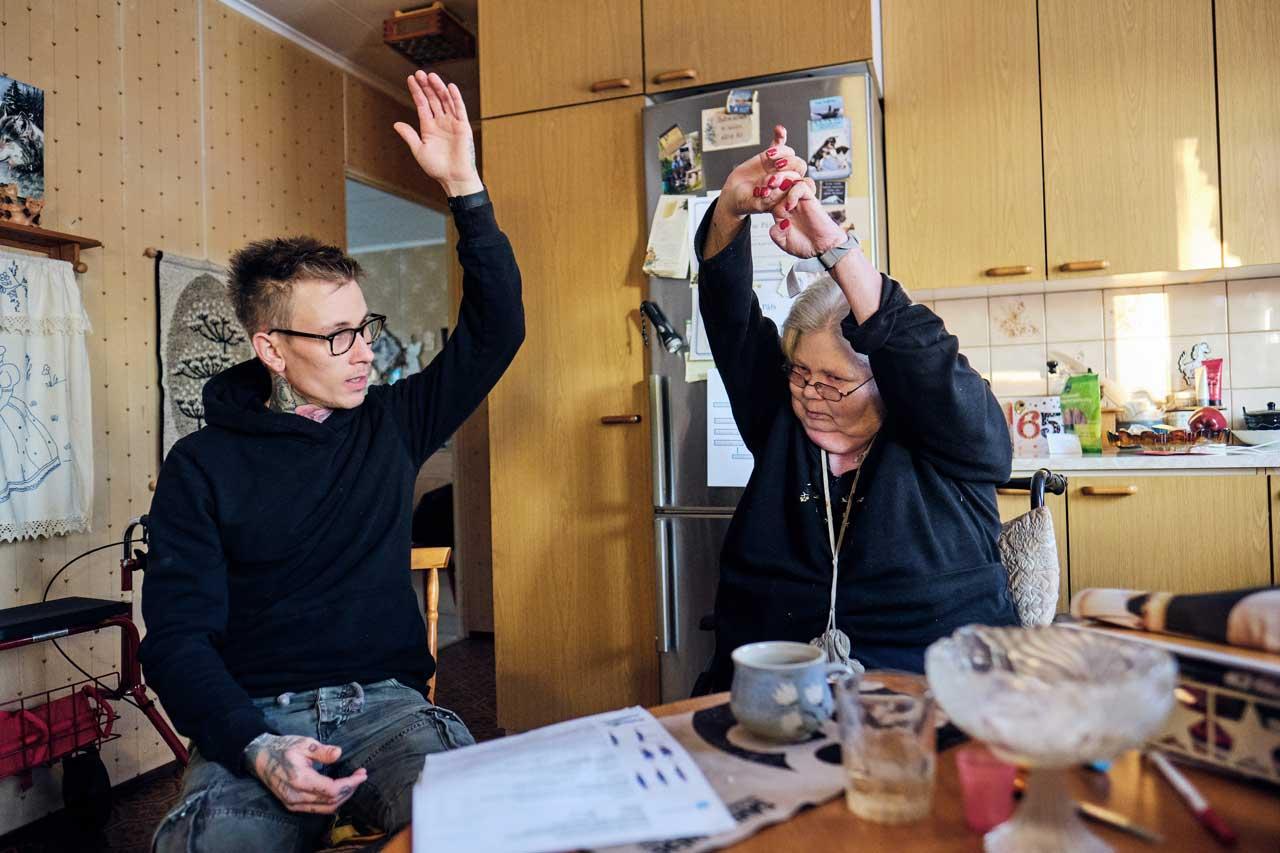 Lähihoitaja Nico Nordblad ja kuntoutettava Anne-Marie Påfs nostavat vasemmat kätensä pystyyn.
