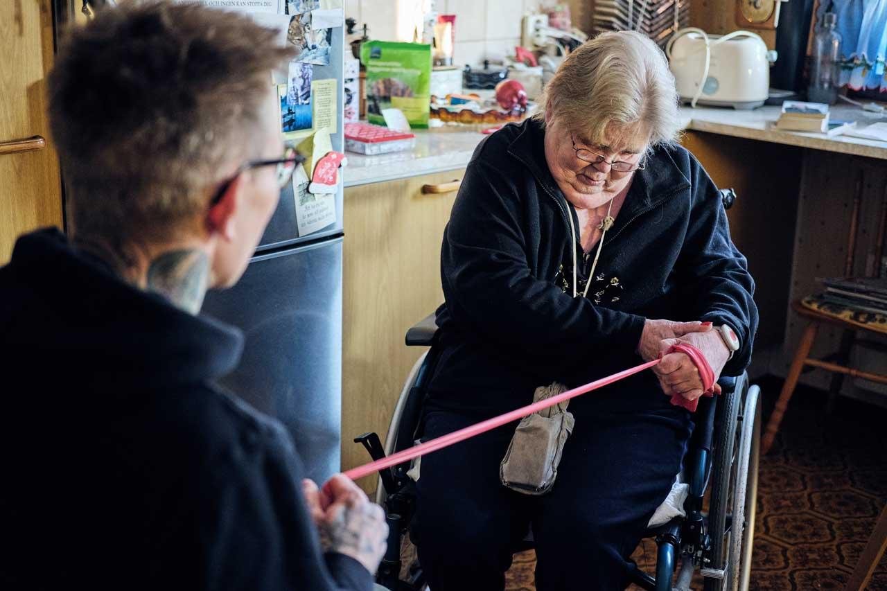 Kuntoutettava Anne-Marie Påfs vetää vasemmalla kädellään kuminauhaa, josta lähihoitaja Nico Nordblad pitää kiinni.