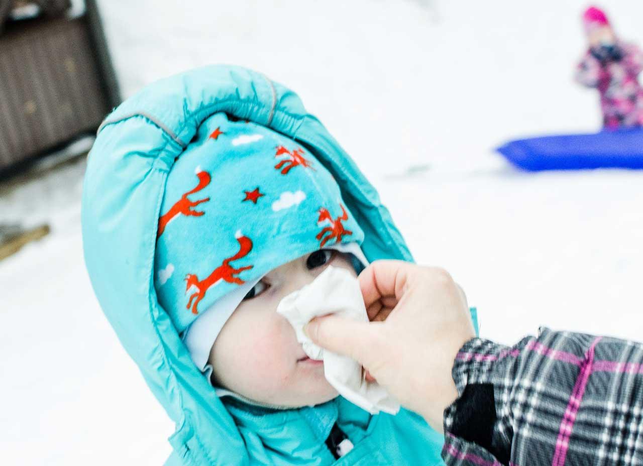 hoitaja pyyhkii lapsen nenää