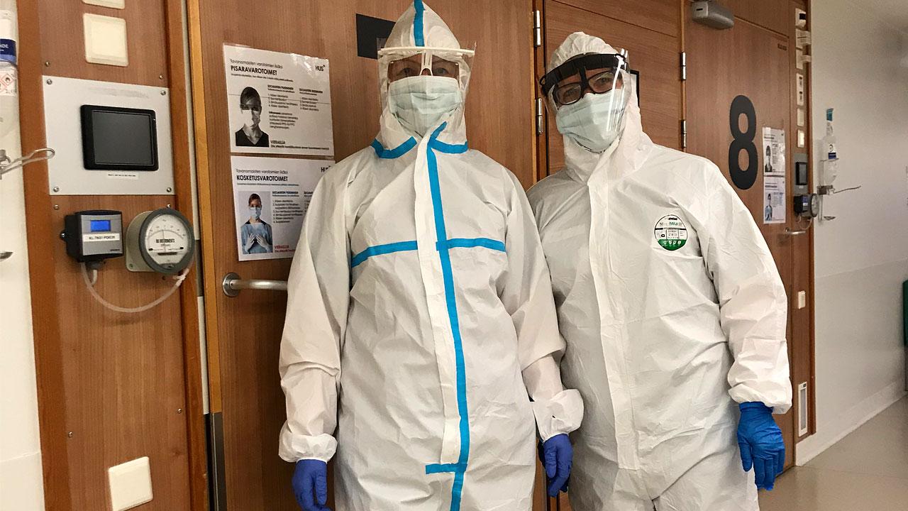 Lähihoitaja ja sairaanhoitaja päällään suojahaalarit, kirurgiset maskit, visiirit ja kumihanskat.