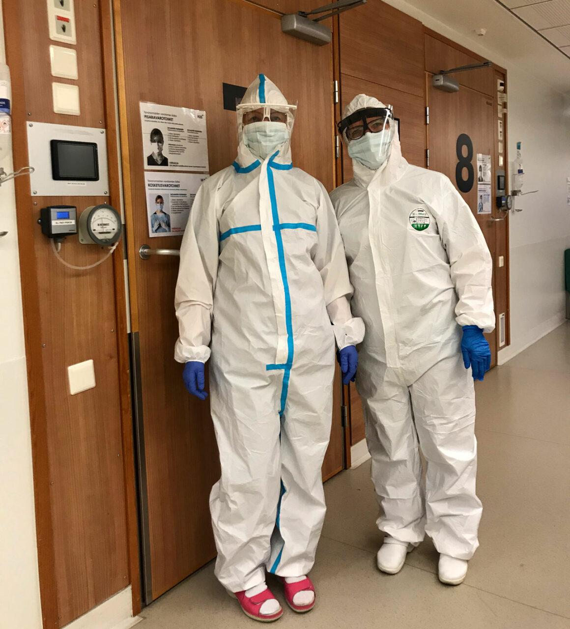 JHL-anslutna närvårdaren Sofia Salokorpi och specialsjukskötaren Leena Timonen iklädda skyddsoverall med kapuschong, kirurgisk mask, visir och gummihandskar..