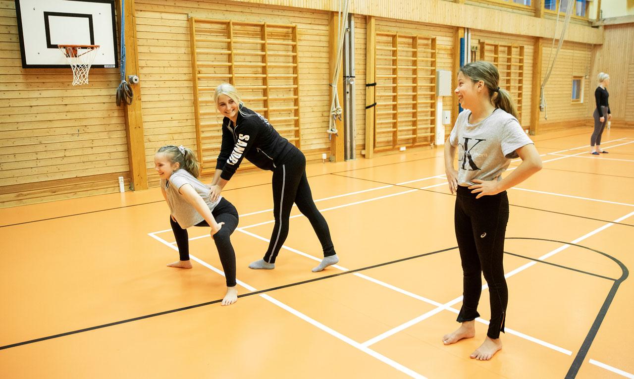 Elevassistenten och JHL-medlemmen Sandra Sirviö instruerar My Wennström och Vivian Keränen på Energy Dance Centers showdansträning.