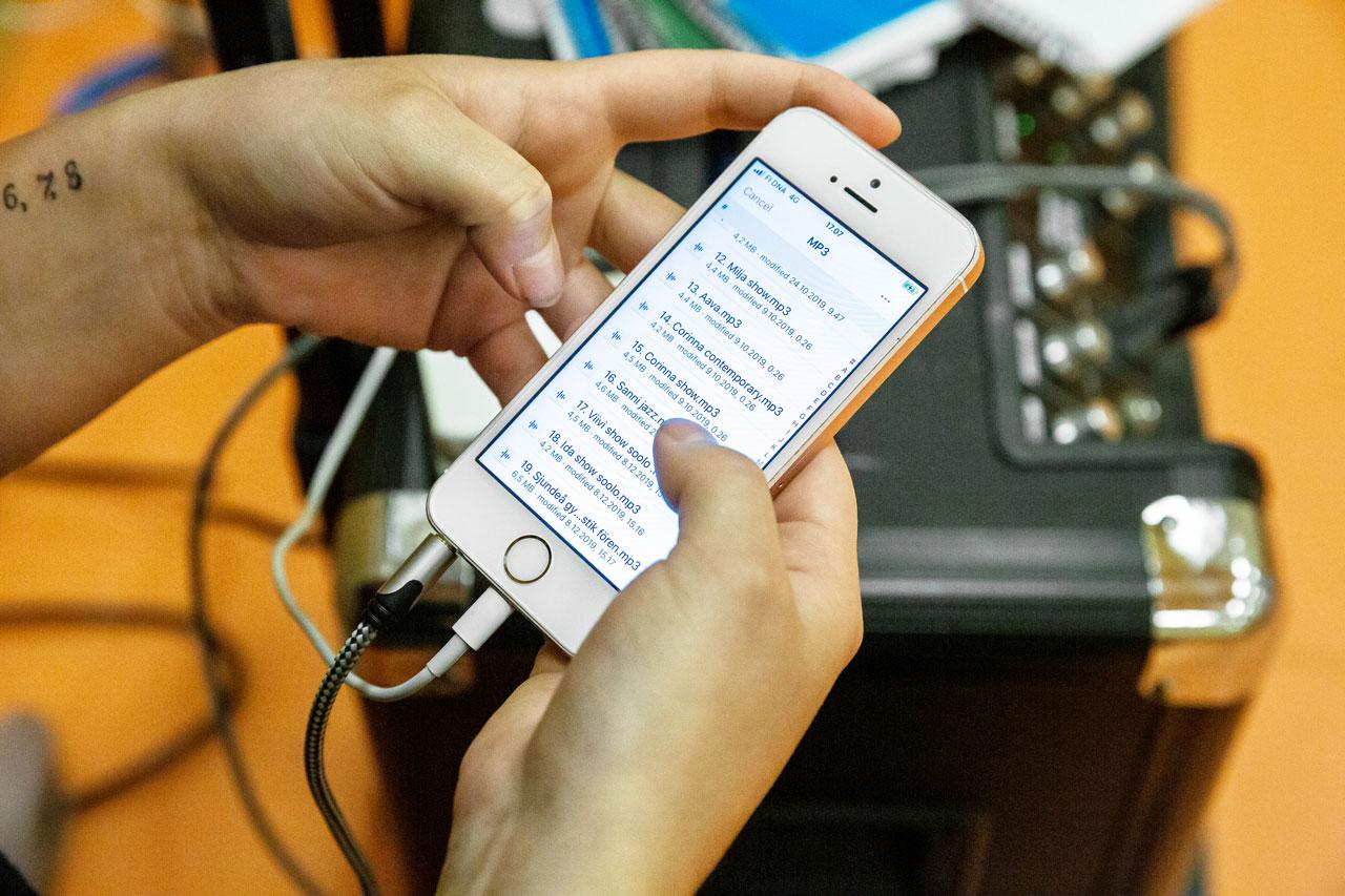 Elevassistenten och JHL-medlemmen Sandra Sirviö väljer musik ur sin telefon på Energy Dance Centers showdansträning.