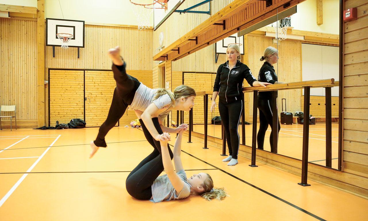 Elevassistenten och JHL-medlemmen Sandra Sirviö ser på när Vivian Keränen och My Wennerström övar akrobatik på Energy Dance Centers showdansövning.
