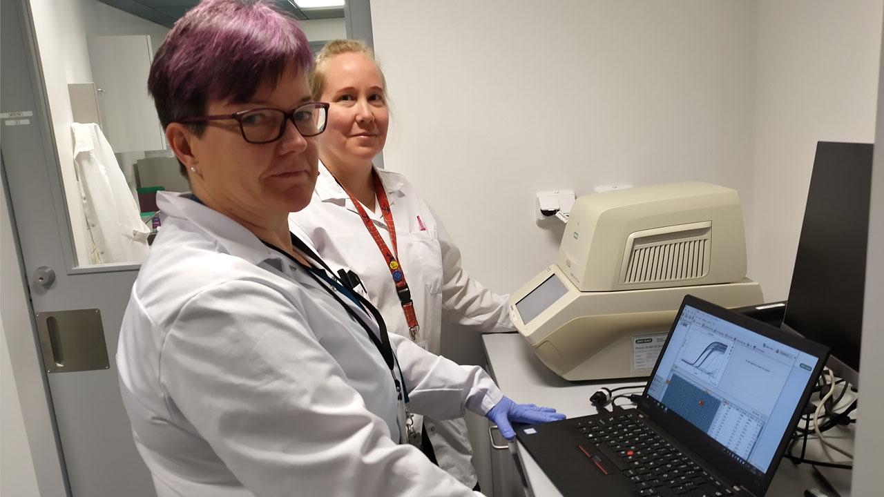 JHL-anslutna laboratoriearbetarna Merja Hautala och Tiina Peltonen kollar resultatet på ett coronavirustest vid en dator.