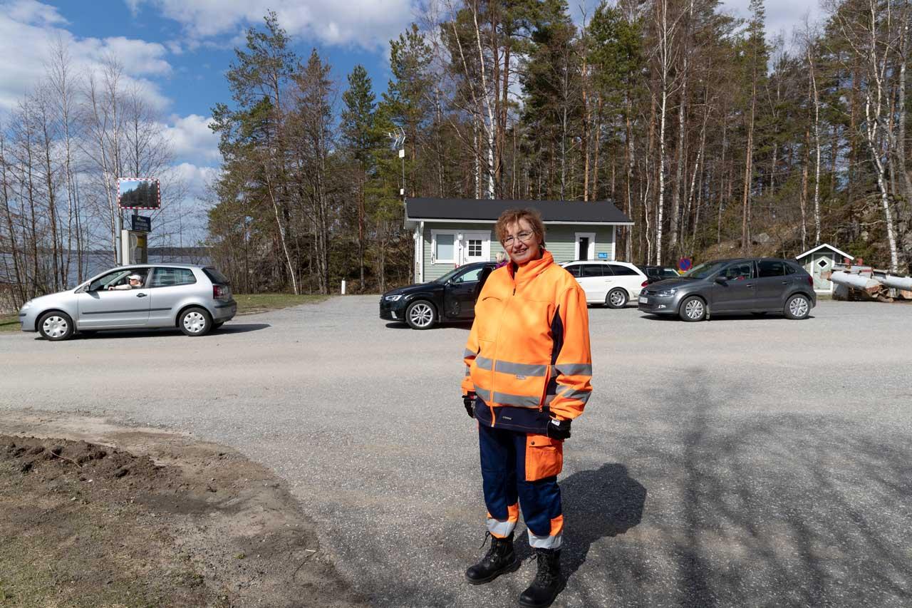 JHL:läinen lossinkuljettaja Tuija Lind lossiin jonottavien autojen ja taukotuvan edessä.
