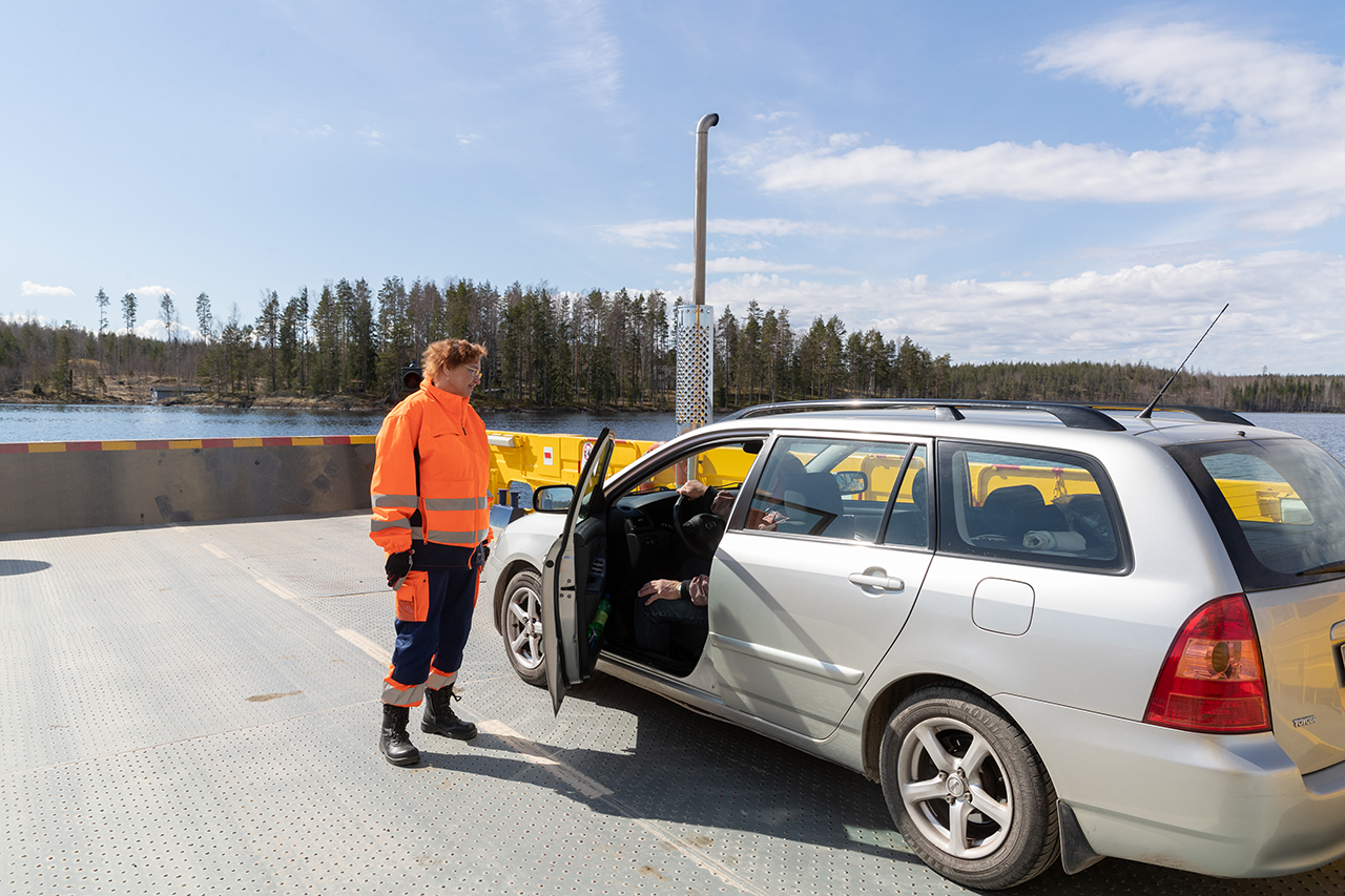JHL:läinen lossinkuljettaja Tuija Lind keskustelee autonkuljettajan kanssa lossin kannella.