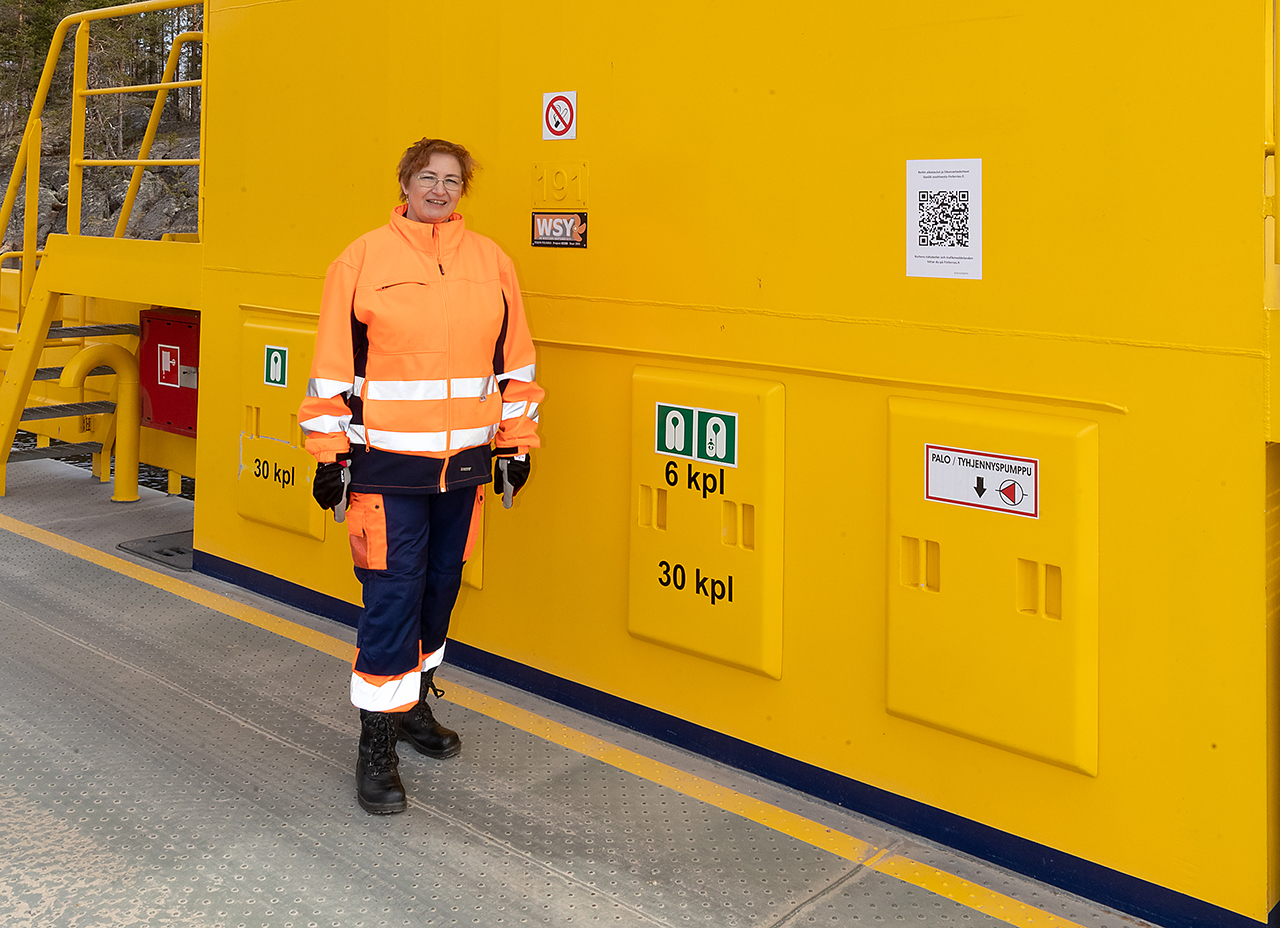 JHL:läinen lossinkuljettaja Tuija Lind lossin kannella pelastusliivivarastojen edessä.