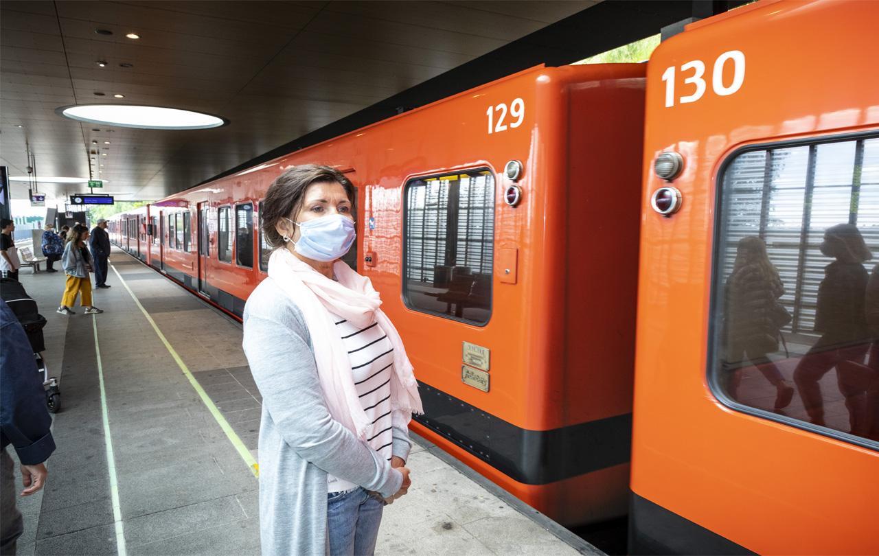 nainen metroasemalla maski kasvoilla