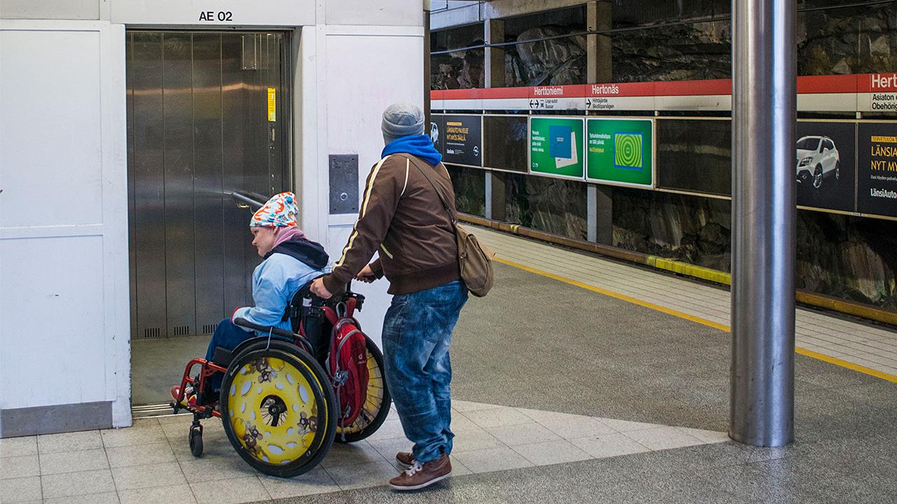 avustaja auttaa vammaista pyörätuolissa