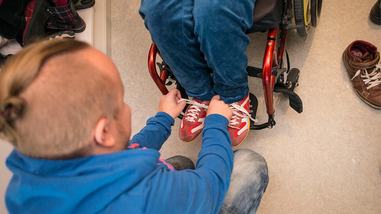 avustaja auttaa pyörätulissa istuvaa