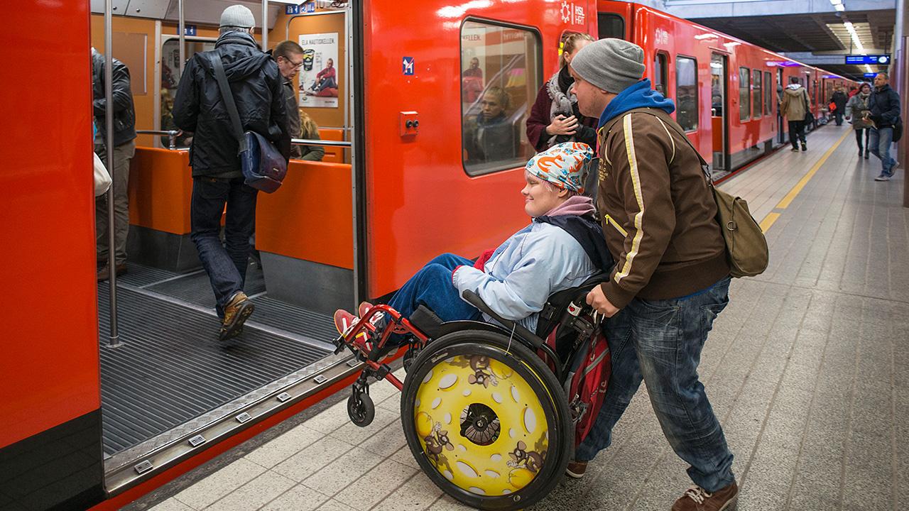 avustaja työntää liikuntakyvytöntä pyörätuolissa