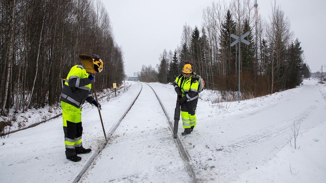 työkoneen kuljettaja Mikko Tammela ja rata-asentaja Krista Mikkonen radan huoltotöissä