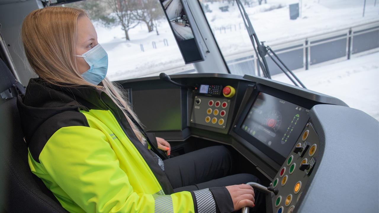 Mona Mäkinen raitiovaunun ohjaamossa