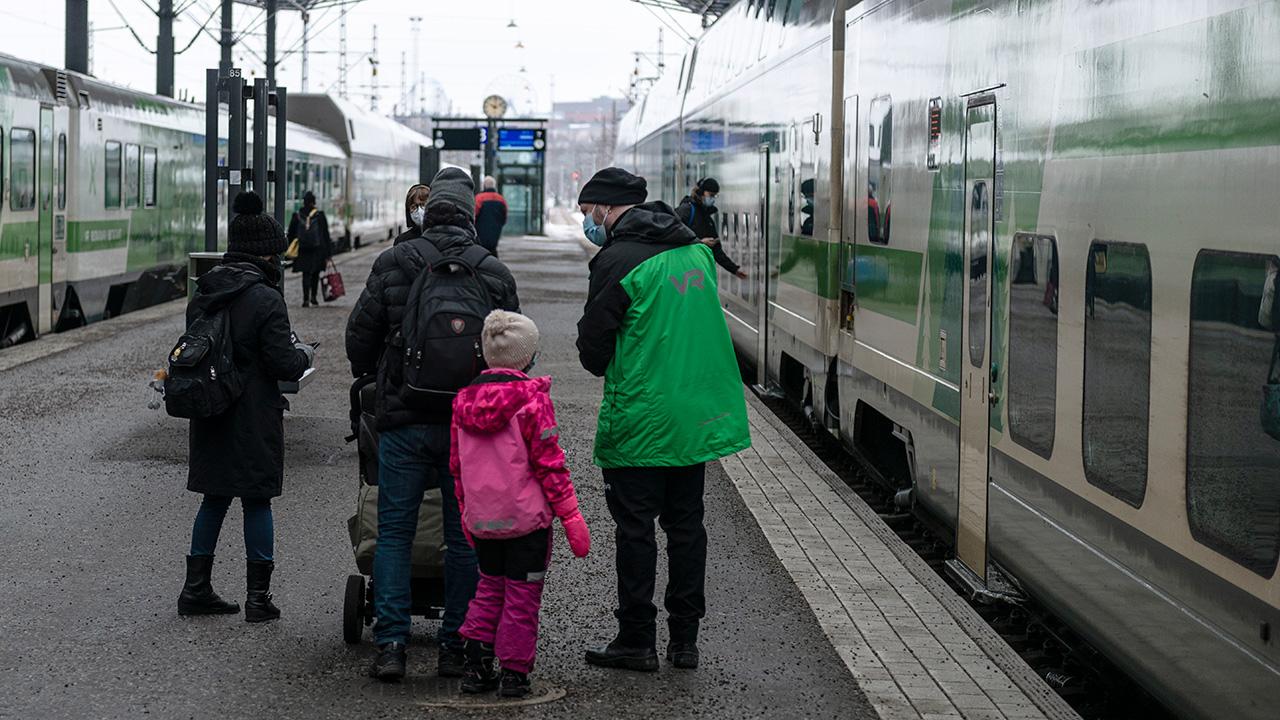 Konduktööri Markus Ollikainen juttelee matkustajien kanssa laiturilla.