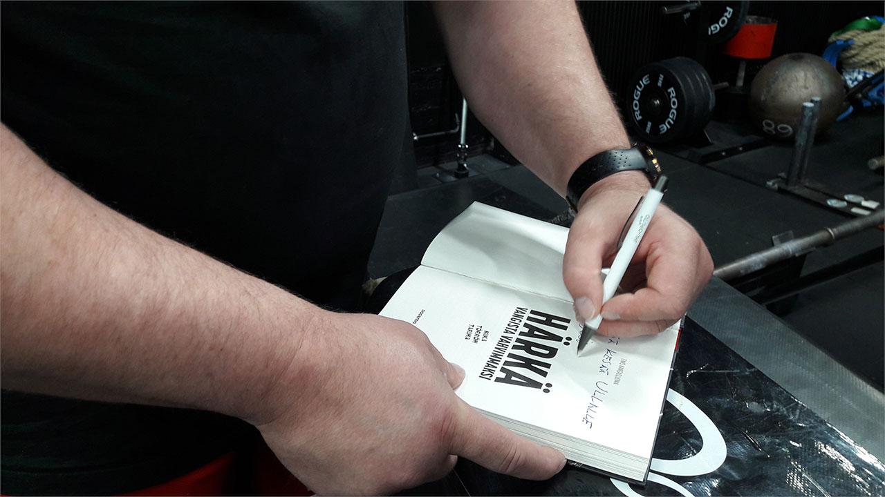 Mika Törrö kirjoittaa omistuskirjoitusta kirjaan